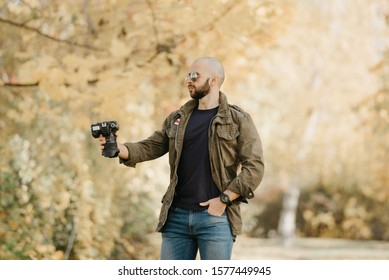 Bald photographer with a beard in aviator sunglasses with mirror lenses, olive cargo military jacket, blue jeans and shirt with digital wristwatch holds out the camera to someone in the forest.