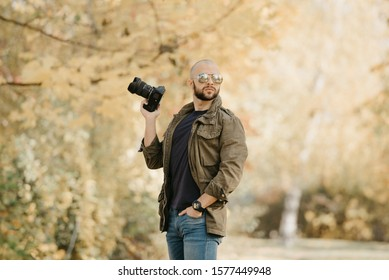 Bald photographer with a beard in aviator sunglasses with mirror lenses, olive military jacket, blue jeans and shirt with digital wristwatch holds the camera in a bent hand and poses in the forest.