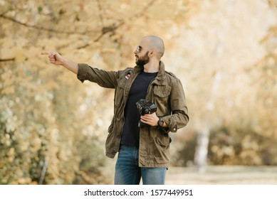 Bald photographer with a beard in aviator sunglasses with mirror lenses, olive cargo combat military jacket, blue shirt with digital wristwatch holds his camera and points a finger to the left.