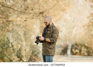 Bald photographer with a beard in aviator sunglasses with mirror lenses, olive cargo military jacket, blue jeans and shirt with digital wristwatch scrolls photos on the camera in the forest.