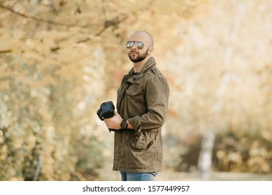 Bald photographer with a beard in aviator sunglasses with mirror lenses, olive cargo military jacket, blue shirt with digital wristwatch holds his camera and waits in the forest in the afternoon.