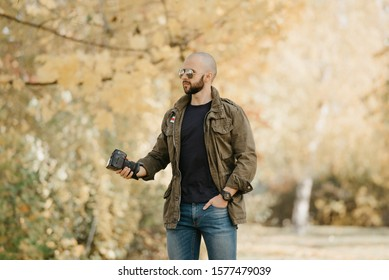 Bald photographer with a beard in aviator sunglasses with mirror lenses, olive cargo military jacket, blue jeans and shirt with digital wristwatch holds the camera by the lens and waits in the forest.
