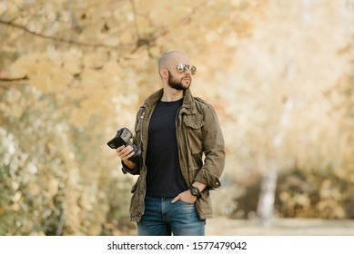 Bald photographer with a beard in aviator sunglasses with mirror lenses, olive military jacket, blue jeans and shirt with digital wristwatch holds the camera by the lens turning his head to the right