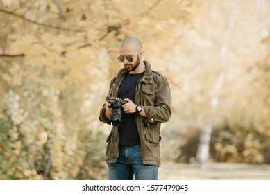Bald photographer with a beard in aviator sunglasses with mirror lenses, olive cargo military jacket, blue jeans and shirt with digital wristwatch checks photos in the camera in the forest.