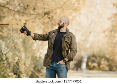 Bald photographer with a beard in aviator sunglasses with mirror lenses, olive cargo military jacket, blue jeans and shirt with digital wristwatch holds out the camera to model in the forest.