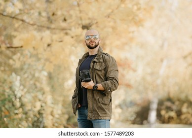 Bald photographer with a beard in aviator sunglasses with mirror lenses, olive military jacket, blue jeans and shirt with wristwatch poses holding his dslr camera and looks straight in the forest