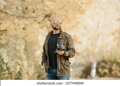 Bald photographer with a beard in aviator sunglasses with mirror lenses, olive military combat jacket, blue jeans and shirt with wristwatch poses with the camera and looks straight in the forest.