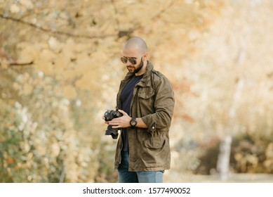 Bald photographer with a beard in aviator sunglasses with mirror lenses, olive cargo military jacket, blue jeans and shirt with digital wristwatch checks system preferences in the camera in the forest