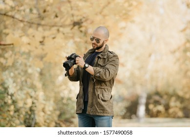 Bald photographer with a beard in aviator sunglasses with mirror lenses, olive cargo military jacket, blue jeans and shirt with digital wristwatch checks system preferences in his camera in the forest