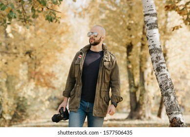 Bald photographer with a beard in aviator sunglasses with mirror lenses, olive military jacket, jeans and shirt with digital wristwatch holds the DSLR camera walks near the battlefield in the forest.