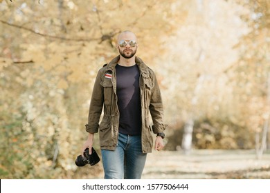Bald photographer with a beard in aviator sunglasses with mirror lenses, olive military combat jacket, blue jeans and shirt with digital wristwatch holds the camera and goes straight in the forest
