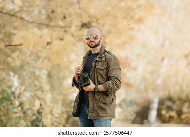 Bald photographer with a beard in aviator sunglasses with mirror lenses, olive military combat jacket, blue jeans and shirt with wristwatch poses holding the dslr camera and looks straight in the fore