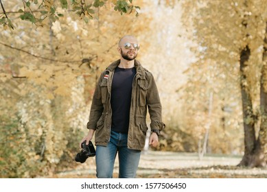 Bald photographer with a beard in aviator sunglasses with mirror lenses, olive military jacket, jeans and shirt with digital wristwatch holds the DSLR camera and goes straight on the battlefield
