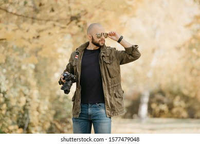 Bald photographer with a beard in olive military combat jacket, blue jeans, and shirt with wristwatch holds the camera and adjusts aviator sunglasses with mirror lenses on his face in the forest.