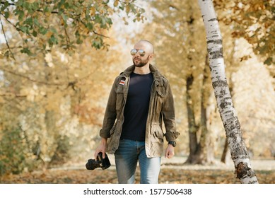 A bald photojournalist with a beard in aviator sunglasses with mirror lenses, olive military jacket, jeans and shirt with wristwatch holds the DSLR camera walks near the battlefield in the forest