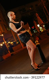 Bald prostitute in the street at the evening