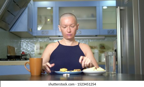 bald sad woman sits at a table in the kitchen with food and pills, reluctantly eats breakfast, feeling nauseous