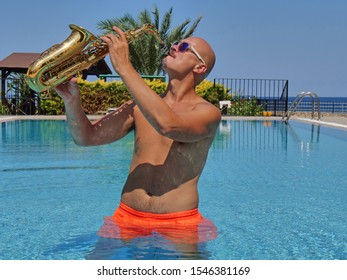 A Bald Saxophonist in orange swimming trunks stands waist-deep in water and plays the golden alto saxophone