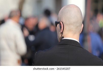 bald security guard with the headset to control people