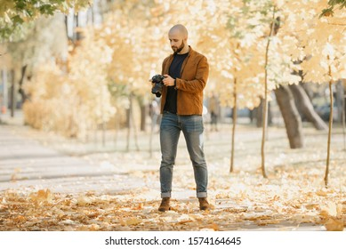 Bald stylish photographer with a beard in a suede leather jacket, blue shirt, jeans, and Chelsea boots holds the camera and looks for the best photo in the park in the afternoon