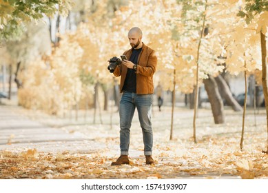 Bald stylish photographer with a beard in a suede leather jacket, blue shirt, jeans, and Chelsea boots holds the camera and looks for something in his cellphone in the park in the afternoon