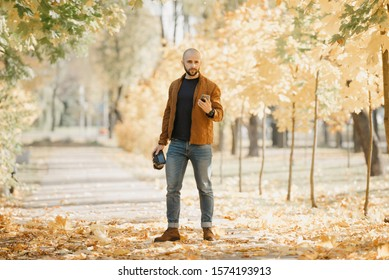 Bald stylish photographer with a beard in a suede leather jacket, blue shirt, jeans, and Chelsea boots holds the camera and the smartphone looks for someone in the park in the afternoon