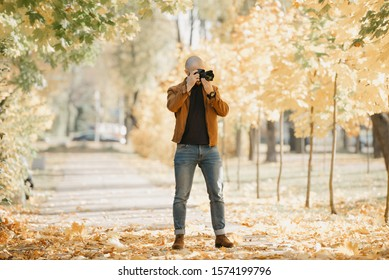 Bald stylish photographer with a beard in a suede leather jacket, blue shirt, jeans, and Chelsea boots takes photos on the camera in the park in the sunny afternoon