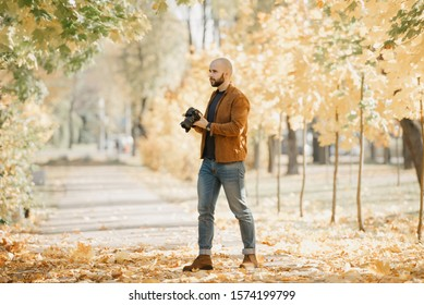 Bald stylish photographer with a beard in a suede leather jacket, blue shirt, jeans, and Chelsea boots holds the camera in the park in the sunny afternoon