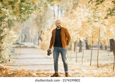Bald stylish photographer with a beard in a suede leather jacket, blue shirt, jeans, and Chelsea boots holds the camera and lays something in a pocket in the park in the afternoon