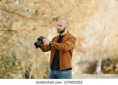 Bald stylish photographer with a beard in a suede leather jacket, blue shirt and jeans looks through photos in the camera in the forest in the sunny afternoon