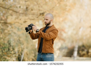 Bald stylish photographer with a beard in a suede leather jacket, blue shirt and jeans looks through photos in his camera in the forest in the sunny afternoon