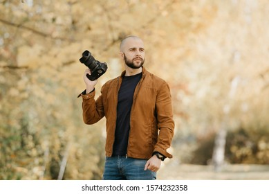 Bald stylish photographer with a beard in a suede leather jacket, blue shirt and jeans with digital wristwatch holds the camera in bent hand in the forest in the sunny afternoon