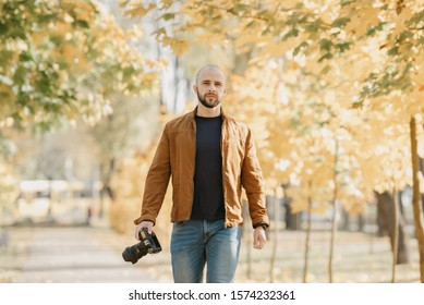 Bald stylish photographer with a beard in a suede leather jacket, blue shirt and jeans holds the camera and goes straight in the park in the sunny afternoon