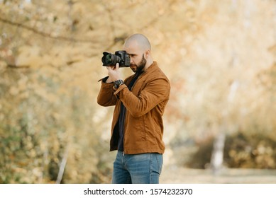 Bald stylish photographer with a beard in a suede leather jacket, blue shirt and jeans with digital wristwatch takes pictures on his camera in the forest in the sunny afternoon