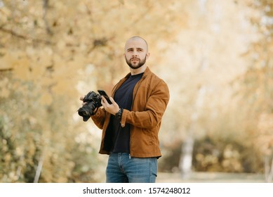 Bald stylish photographer with a beard in a suede leather jacket, blue shirt, jeans with wristwatch holds the camera in bent hand and smartphone in the forest in the afternoon