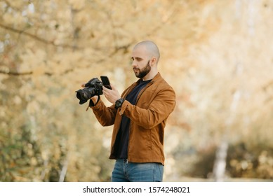 Bald stylish photographer with a beard in a suede leather jacket, blue shirt, jeans with analog wristwatch holds the camera and looks for something in his smartphone in the forest in the afternoon