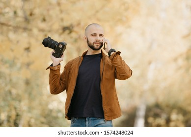 Bald stylish photographer with a beard in a suede leather jacket, blue shirt, jeans with wristwatch holds the camera in bent hand and calls somebody by his smartphone in the park in the afternoon