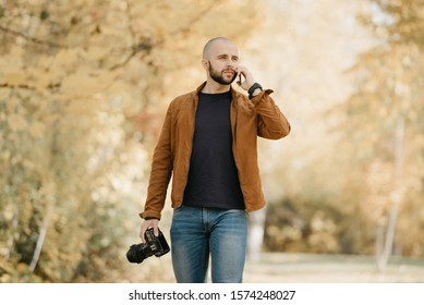 Bald stylish photographer with a beard in a suede leather jacket, blue shirt, jeans with analog wristwatch holds the camera and calls somebody by his smartphone in the forest in the afternoon