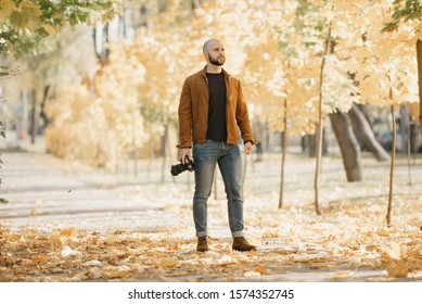Bald stylish photographer with a beard in a suede leather jacket, blue shirt, jeans, and Chelsea boots holds the camera and looks for a location in the park in the afternoon
