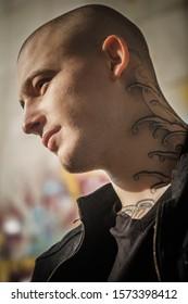 Bald tatouait un jeune homme brutal avec un tatouage sur le cou. Jeune homme beau, portant une veste en denim noir et un t-shirt noir. Gros plan, visage, portrait d'un jeune homme séduisant.