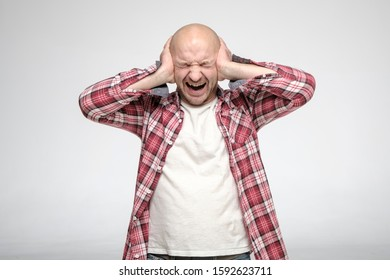 Bald, unshaven man in stress, he covered his ears with hands so as not to hear sounds annoying him and screams loudly. Isolated on white background.