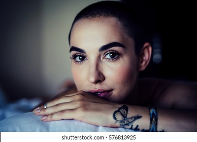 bald woman with incredible beautiful eyes gentle natural vision in the morning in bed enjoying. the concept of a happy life, the concept of happy woman