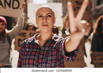 Bald woman protesting outdoors and showing a peace hand sign. Woman with group of people protesting outdoors on city street.