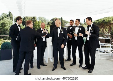 Bald-headed groom drinks wine with his friends under white pavilion outside