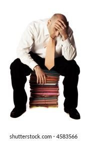 Balding man seated on stack of colorful files in white shirt and tie, head in hands, isolated on white background