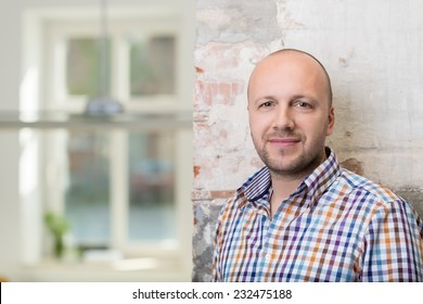 Balding middle-aged man in a checked shirt standing against a painted brick wall looking at the camera with a friendly smile, with copyspace