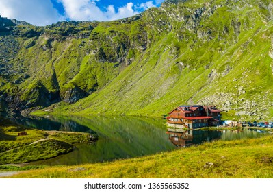 Balea lake near Transfagarasan road in the Carpathian Mountains, Romania, Eastern Europe. Wood cabin, chalet, hotel, cottage. Glacial, green grass, rocks, summer vacation, landscape.