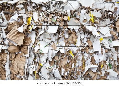 Bales of cardboard and box board with strapping wire ties in focus