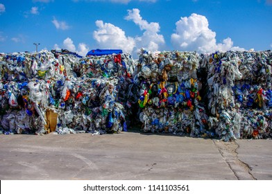 Bales of rigid and film plastics collected and stacked in outdoor storage waiting for recycling.