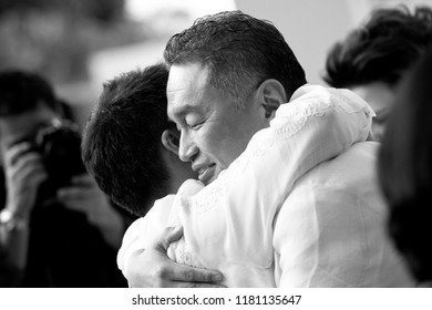 Bali 6 June 2012 - Black and white photo while son hug his dad after having wedding ceremony in Bali Indonesia, dad looks so happy for seeing his son for getting married